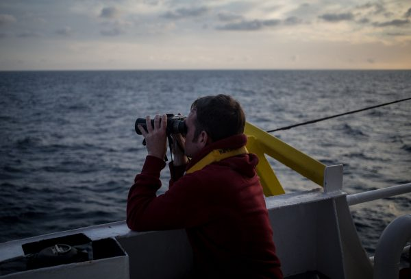 One of the crew members of the Dutch-flagged rescue vessel Sea Watch 3 keeps a watch on the sea with binoculars