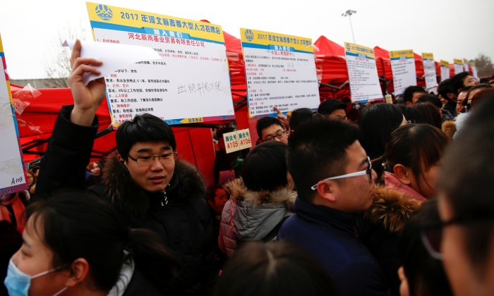 Recruiters and job seekers crowd an open air employment fair for college graduates and the general public in the center of Shijiazhuang, Hebei Province, China on Feb. 6, 2017. (Thomas Peter/Reuters)