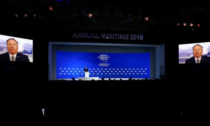 Borge Brende, President of World Economic Forum stands on a stage while U.S. Secretary of State Mike Pompeo is seen on screens as he addresses attendees via satellite, during the World Economic Forum (WEF) annual meeting in Davos, Switzerland on Jan. 22, 2019. (Arnd Wiegmann/Reuters)