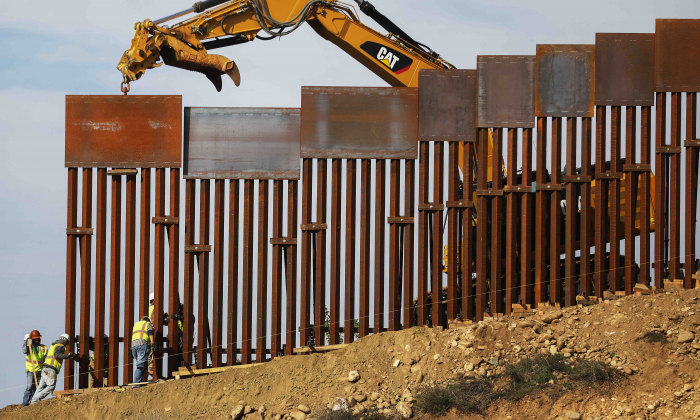 A construction crew installs new sections of the U.S.-Mexico border barrier replacing smaller fences as seen from Tijuana, Mexico, on Jan. 11, 2019. (Mario Tama/Getty Images)