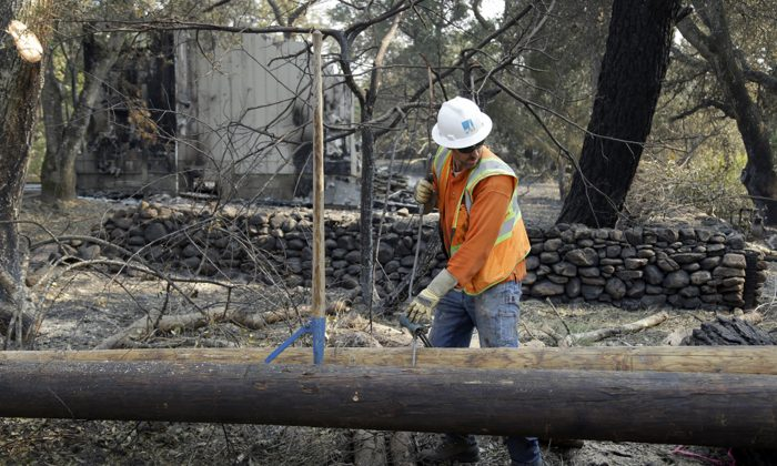 In this file photo, a Pacific Gas & Electric worker replaces power poles destroyed by wildfires in Glen Ellen, Calif., on Oct. 18, 2017. (AP Photo/Ben Margot, file)
