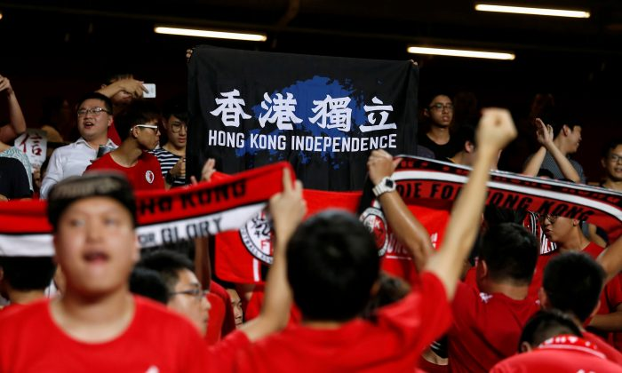 Football Soccer—Hong Kong v Malaysia —AFC Asian Cup Qualifiers in Hong Kong, China on Oct. 10, 2017.  Hong Kong fans hold a protest banner and turn their backs during the Chinese national anthem. (Bobby Yip/Reuters)