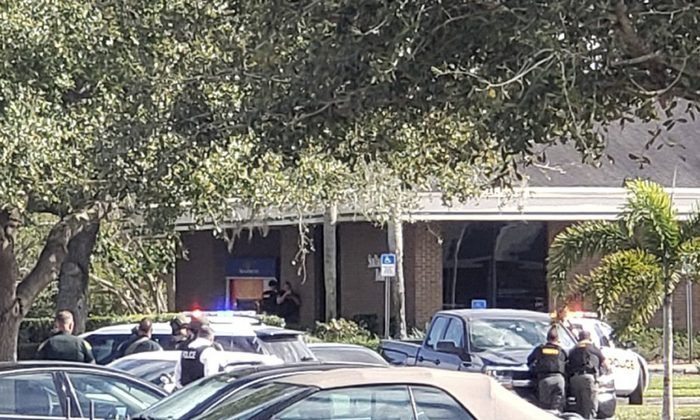 Law enforcement officials take cover outside a SunTrust Bank branch, in Sebring, Fla., on Jan. 23, 2019. (The News Sun via AP)