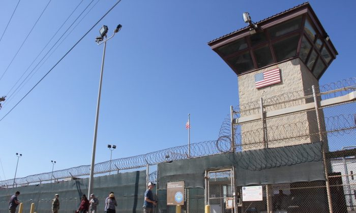 People walk past a guard tower outside the fencing of Camp 5 at the U.S. military prison in Guantanamo Bay, Cuba, on Jan. 26, 2017. (THOMAS WATKINS/AFP/Getty Images)
