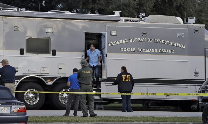 Law enforcement officials climb out a FBI mobile command center in Sebring, Fla, on Jan. 23, 2019. (Chris O'Meara/AP Photo)