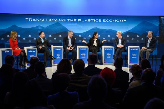 panel of speakers sitting onstage with blue background at davos