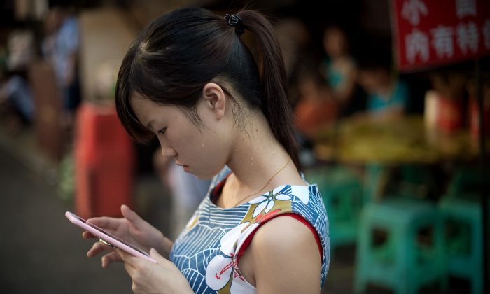 A young woman looks at her smartphone in Chongqing City on Aug. 24, 2016.  (NICOLAS ASFOURI/AFP/Getty Images)