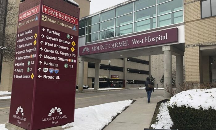 "In this Jan. 15, 2019 file photo, the main entrance to Mount Carmel West Hospital is shown in Columbus, Ohio. The Columbus-area Mount Carmel Health System said a doctor's orders for potentially fatal doses of pain medicine given to over two dozen patients were carried out by what he calls ""a small number of good people who made poor decisions."" Mount Carmel Health System said it fired the intensive care doctor, put six pharmacists and 14 nurses on paid leave pending further review and reported its findings to authorities. (AP Photo/Andrew Welsh Huggins, File)"