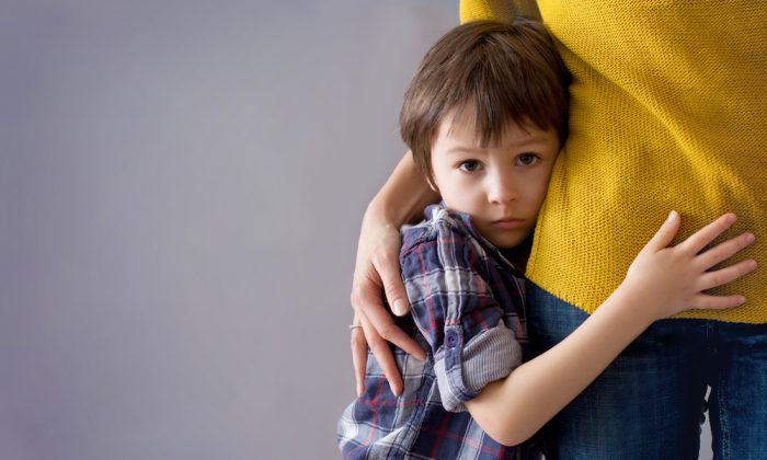 Sad little boy hugging his mother. (Shutterstock)