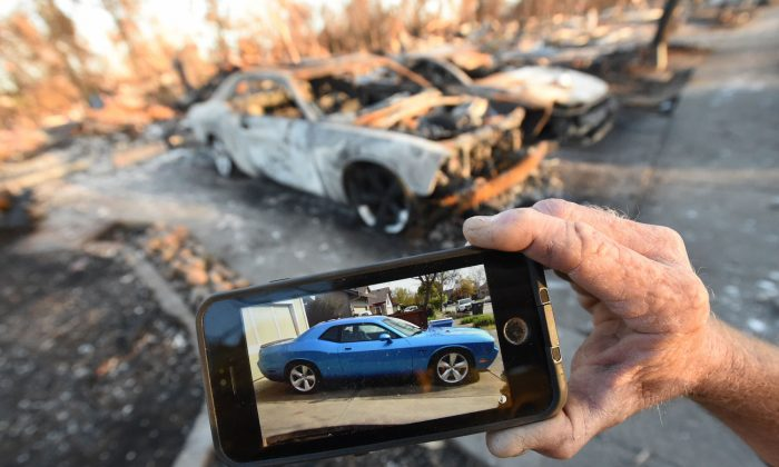 Car collector Gary Dower holds up a photo showing his 2010 Dodge Challenger Limited Edition SRT8 before it burned at his home in Santa Rosa, Calif., on Oct. 20, 2017. (Josh Edelson/AFP/Getty Images)