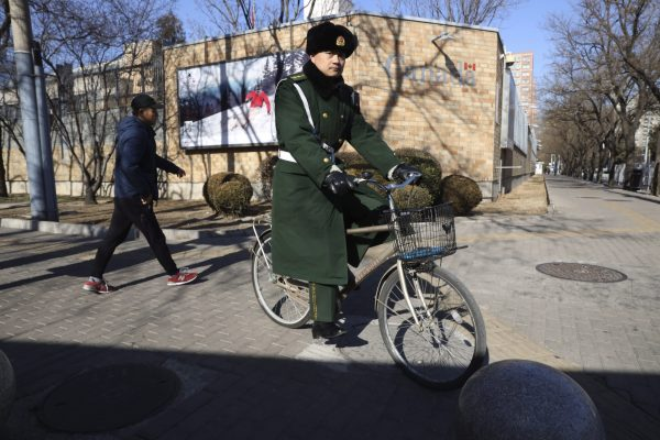 A Chinese paramilitary policeman rides past the Canadian embassy in Beijing, China, on Jan. 16, 2019. (AP Photo/Ng Han Guan)