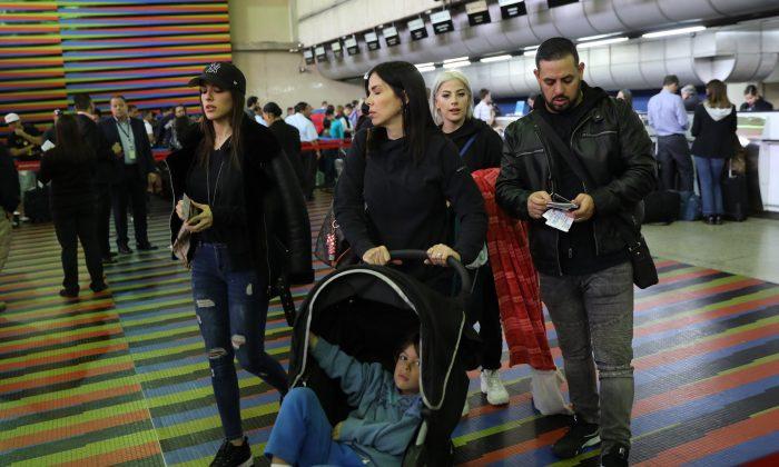 U.S. embassy employees and their families prepare to depart Simon Bolivar international airport in La Guaira, Venezuela, on Jan. 25, 2019. (Rodrigo Abd/AP Photo)