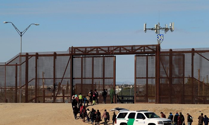 Illegal aliens from Central America are seen escorted by U.S. Customs and Border Protection (CBP) officials after crossing the border from Mexico to surrender to the officials in El Paso, Texas, on Dec. 3, 2018. (Jose Luis Gonzalez/Reuters)