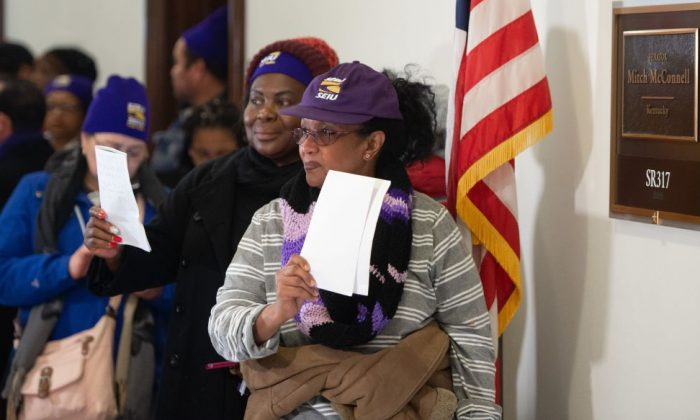 Furloughed contract workers, including security officers and custodians who have not been paid during the partial government shutdown, hold unpaid bills to present to the office of Senate Majority Leader Mitch McConnell on Capitol Hill in Washington, DC, Jan. 16, 2019. (Saul Loeb/AFP/Getty Images)