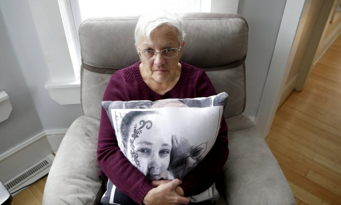 In a photo taken Friday, Jan. 18, 2019, Deborah Fuller poses for a photograph for The Associated Press with a pillow showing a photo of her late daughter, Sarah Fuller, left, who passed of a prescription drug overdose, and her during an interview in her home in West Berlin, N.J. The trial of the Insys Therapeutics Inc. founder John Kapoor, who accused of scheming to bribe doctors into prescribing a powerful painkiller, is putting a spotlight on the nation's deadly opioid crisis. (AP Photo/Julio Cortez)