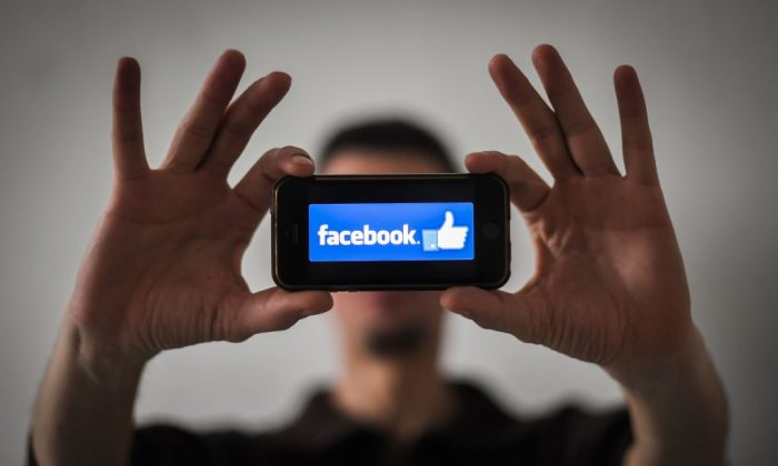 A man shows the logo of social network Facebook displayed on a smartphone in Nantes, France, on Jan. 15, 2019. (Loic Venance/AFP/Getty Images)