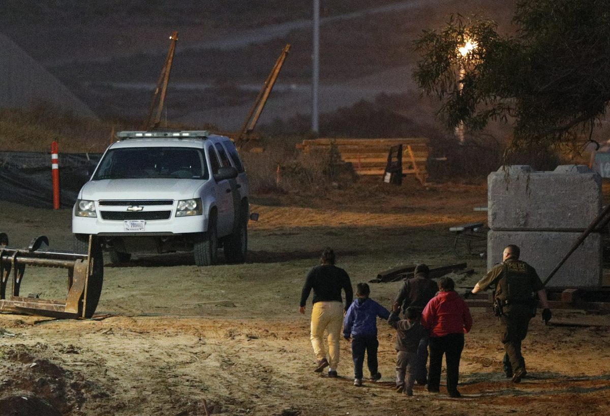 Migrants are escorted by a U.S. Border Patrol agent