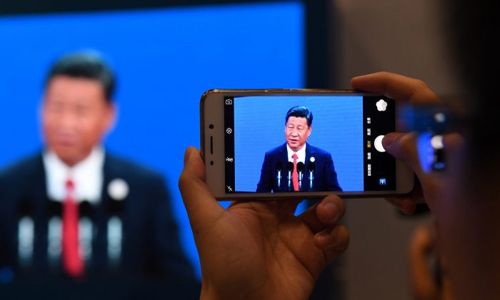 A journalist takes a photo of a live feed of Chinese leader Xi Jinping speaking in Beijing on May 14, 2017. (GREG BAKER/AFP/Getty Images)