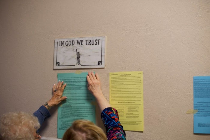 In God We Trust plaque above voting notices.