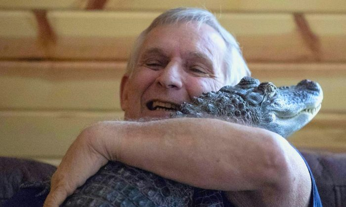 Joie Henney, 65, hugs his emotional support alligator named Wally inside their home in York Haven, Pa. on Jan. 22, 2019. (Heather Khalifa/The Philadelphia Inquirer/AP)