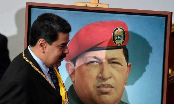 Venezuelan President Nicolas Maduro passes by a portrait of late Venezuelan President Hugo Chavez as he arrives to speak before the Constituent Assembly, at the Federal Legislative Palace in Caracas on Jan. 14, 2019. (Federico Parra/AFP/Getty Images)