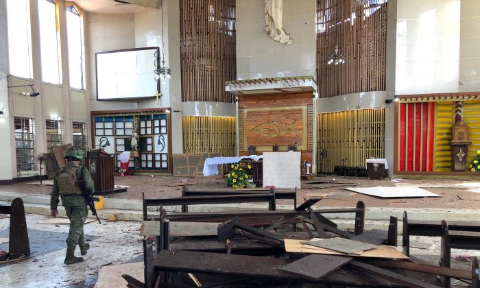 A Philippine Army member inspects the damage inside a church after a bombing attack in Jolo, Sulu province, Philippines January 27, 2019. Armed Forces Of The Philippines (Western Mindanao Command/Handout via Reuters)