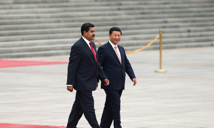 Chinese leader Xi Jinping (R) accompanies Venezuela's President Nicolas Maduro (L) to view an honor guard during a welcoming ceremony outside the Great Hall of People in Beijing on Sept. 22, 2013. (Lintao Zhang/Getty Images)