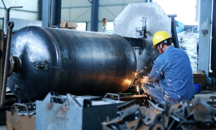 A worker welds a pressure vessel at a company manufacturing industrial equipment in Nantong, Jiangsu Province, China on June 19, 2018. (Reuters)