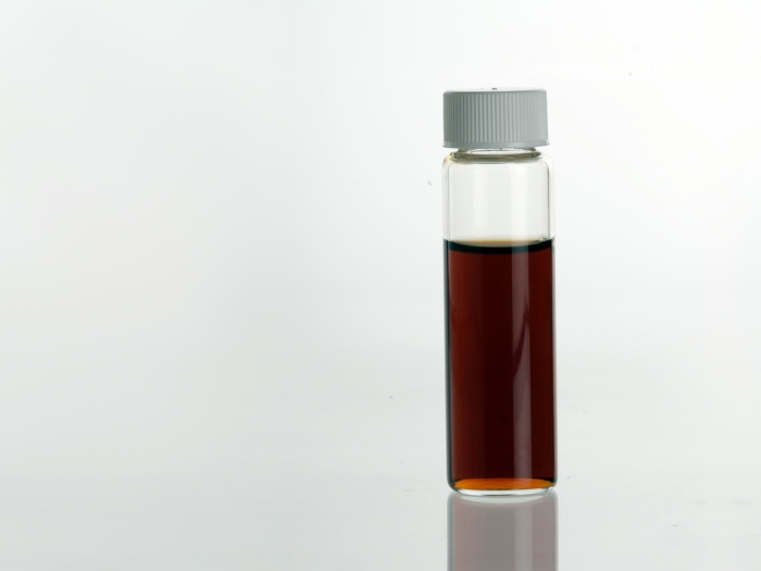 Vanilla (Vanilla planifolia) Extract in clear glass vial.