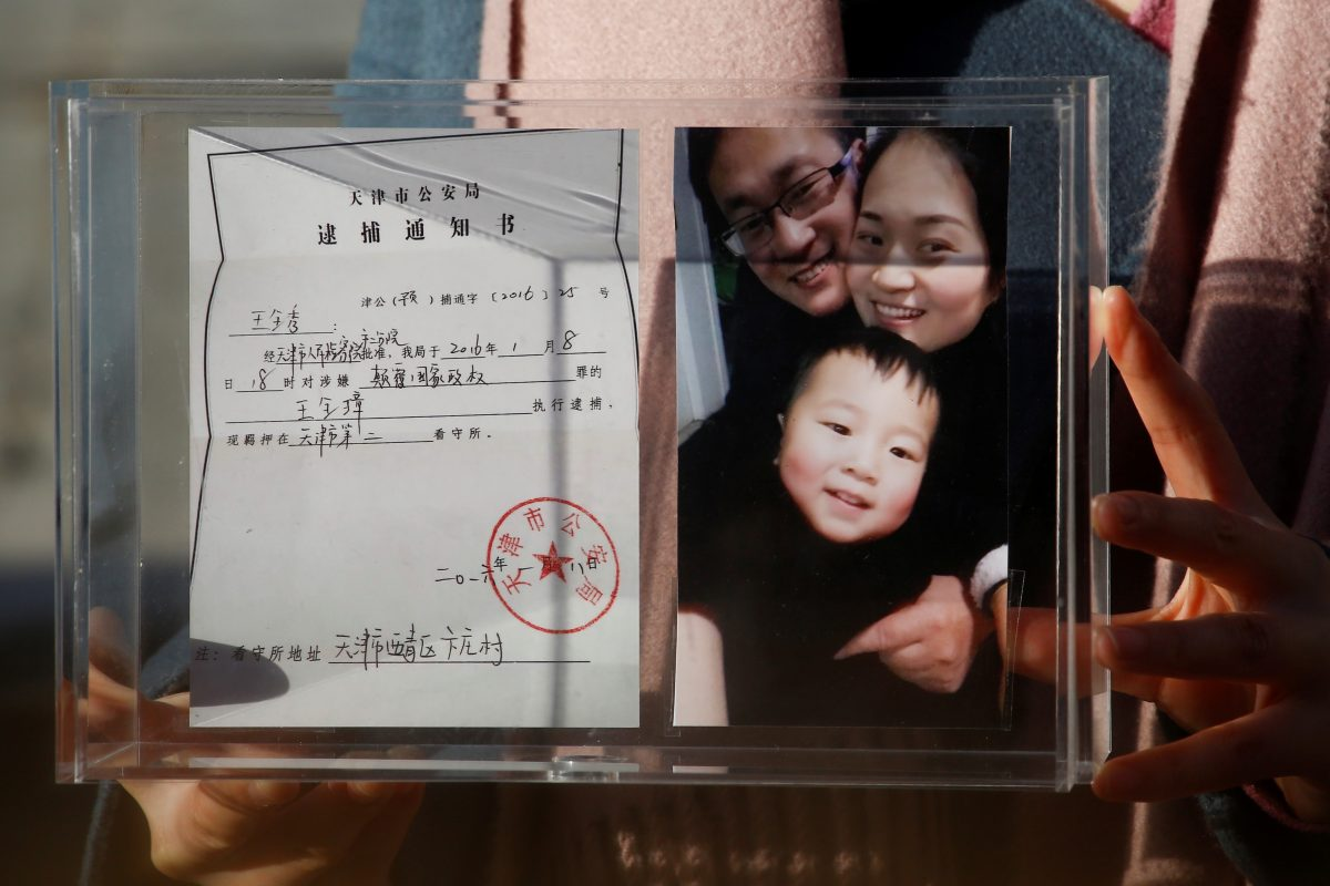 FILE PHOTO: Li Wenzu holds family picture and husband's detention notice in Beijing