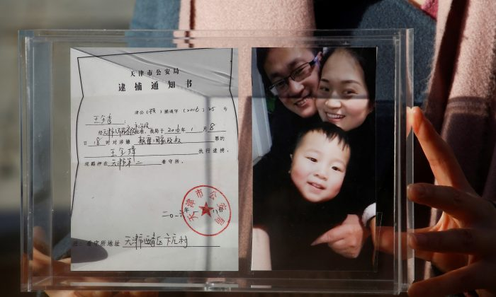 Li Wenzu, the wife of prominent Chinese rights lawyer Wang Quanzhang, holds a box with a family picture and the detention notice for her husband before shaving her head in protest in Beijing, China, Dec. 17, 2018.  (Thomas Peter/Reuters)