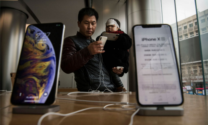 A Chinese man holds his son as they look at iPhones on display at an Apple Store on Jan. 7 in Beijing. (Kevin Frayer/Getty Images)
