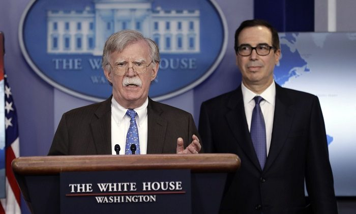 National security adviser John Bolton (L) and Treasury Secretary Steven Mnuchin during a press briefing at the White House, on Jan. 28, 2019. (Evan Vucci/AP Photo)