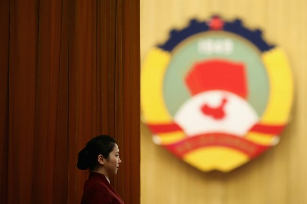 A hostess stands by the curtain as delegates entering the meeting room before the plenary session of the Chinese People's Political Consultative Conference at the Great Hall of the People on March 11, 2013 in Beijing, China. (Feng Li/Getty Images)