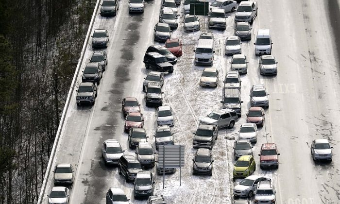 Abandoned cars at I-75 headed northbound near the Chattahoochee River overpass are piled up in the median of the ice-covered interstate after a winter snow storm, in Atlanta on Jan. 29, 2014. (AP Photo/David Tulis, File)