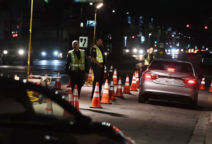 LAPD police check drivers at a DUI checkpoint.
