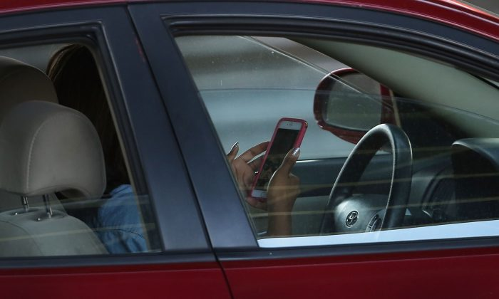 A driver uses a phone while behind the wheel of a car in New York City on April 30, 2016. (Photo by Spencer Platt/Getty Images)
