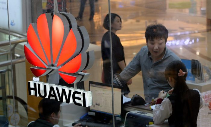 An employee uses a computer as she deals with a customer at a Huawei store in Beijing on March 24, 2014. (MARK RALSTON/AFP/Getty Images)