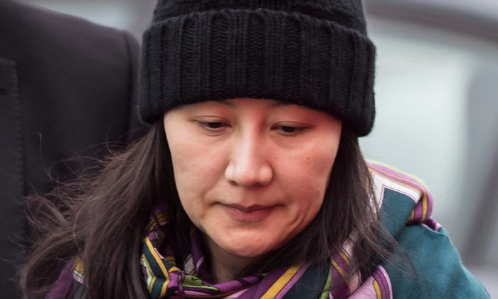 Huawei chief financial officer Meng Wanzhou is escorted by her private security detail while arriving at a parole office in Vancouver on Dec. 12, 2018. (THE CANADIAN PRESS/Darryl Dyck)