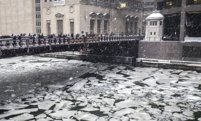Pedestrians cross an icy Chicago River on Madison St. near the Civic Opera House in Chicago, on Jan. 28, 2019. (Rich Hein/Chicago Sun-Times via AP)