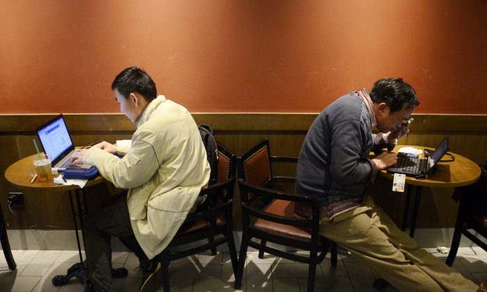 Two Chinese men use their laptop computers at a cafe in Beijing on Nov. 2, 2012.  A government-backed campaign to assert greater control over social media has lead to increased self-censorship by some of China's most influential bloggers, chilling political discourse in the country.   (Wang Zhao/AFP/Getty Images)