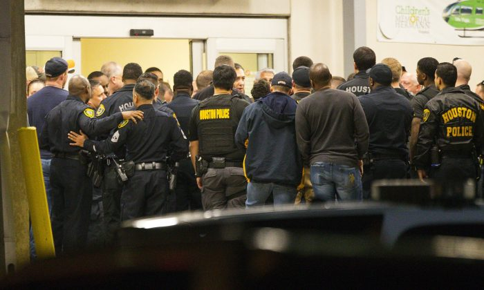 Officers listen as Houston Police Chief Art Acevedo comes outside of the emergency department at Memorial Hermann Hospital after visiting injured officers in the Texas Medical Center, in Houston, on Jan. 28, 2019. (Mark Mulligan/Houston Chronicle via AP)