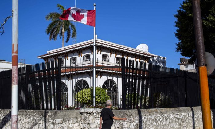 In this April 17, 2018 file photo, a  man walks beside Canada's embassy in Havana, Cuba. Canada has confirmed 14 cases of mysterious health problems since early 2017.  (AP Photo/Desmond Boylan, File)