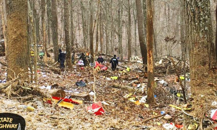 In this photo provided by the Ohio State Highway Patrol, authorities survey the scene of wreckage where a medical helicopter crashed in a remote wooded area in Brown Township, Ohio, on its way to pick up a patient, Jan. 29, 2019. (Ohio State Highway Patrol via AP)