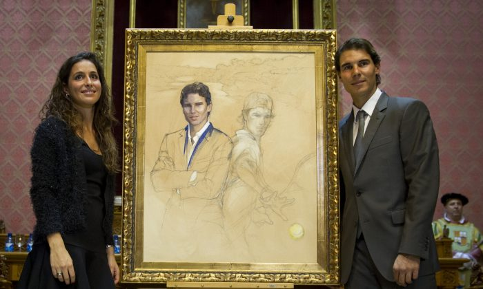 Spanish tennis pro Rafael Nadal (R) and fiancee Xisca Perello pose at a painting depicting Nadal in Palma de Mallorca, Spain, on Dec. 1, 2014. (Jaime Reina/AFP/Getty Images)