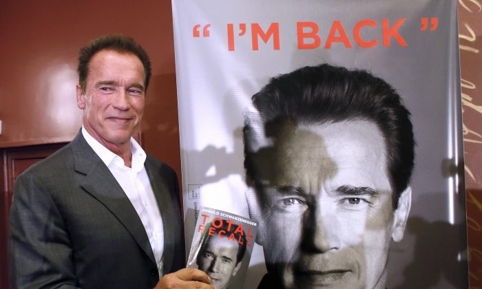 "U.S. actor and former California Gov. Arnold Schwarzenegger holds his autobiography titled ""Total Recall"" after a press conference, on Oct. 12, 2012, in Paris. (Patrick Kovarik/AFP/Getty Images)"