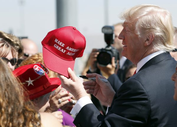 """President Donald Trump hands a signed """"Make America Great Again"""