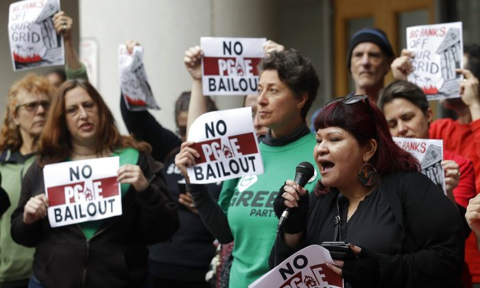 Jessica Tovar, right, speaks at a rally before a California Public Utilities Commission meeting in San Francisco, Monday, Jan. 28, 2019. California regulators have approved a measure allowing Pacific Gas & Electric Corp. to immediately obtain credit and loans while the company is under Chapter 11 bankruptcy protection. (AP Photo/Jeff Chiu)