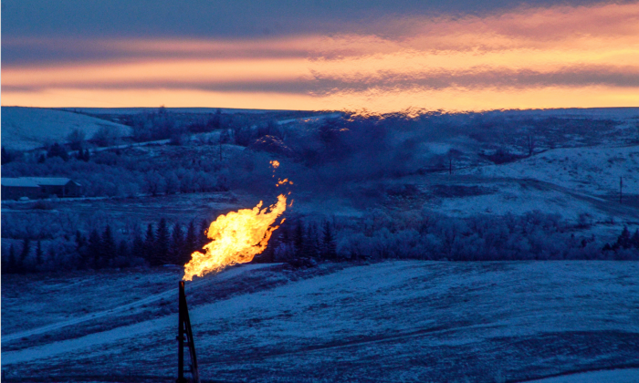 A natural gas flare on an oil well pad burns as the sun sets outside Watford City, N.D., on Jan. 21, 2016. (REUTERS/Andrew Cullen)