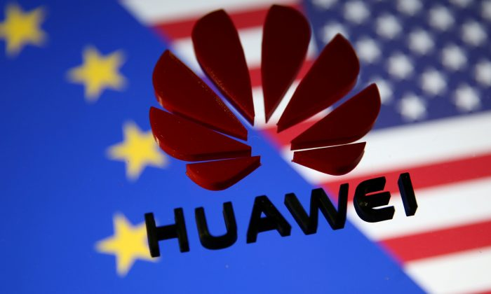 A 3D printed Huawei logo is placed on glass above a display of EU and U.S. flags in this illustration taken on Jan. 29, 2019. (Dado Ruvic/Reuters)